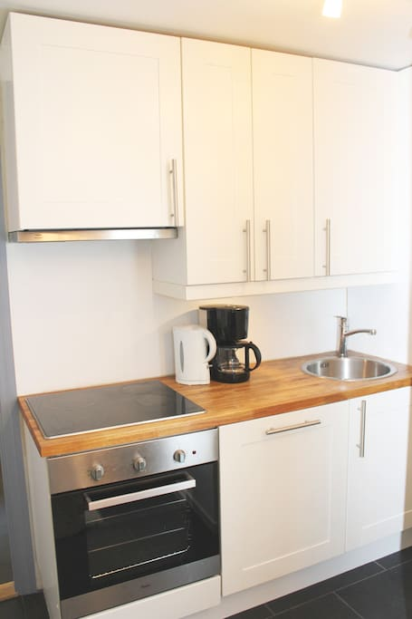 Small kitchen with fridge, dishwasher, stove, coffee maker etc.