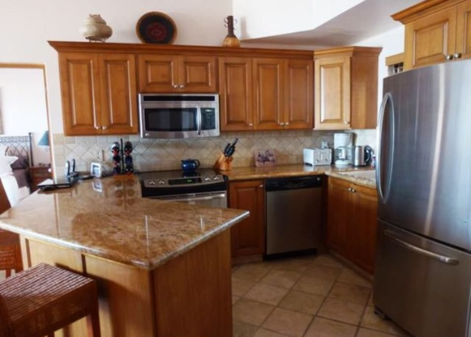An ideal kitchen for cooking and entertaining guests. Kitchen includes an oven, microwave, dishwasher, coffee maker, and fridge/ freezer.