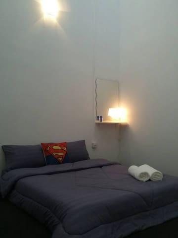 Bedroom 2. Queen bed and bedside lamp.