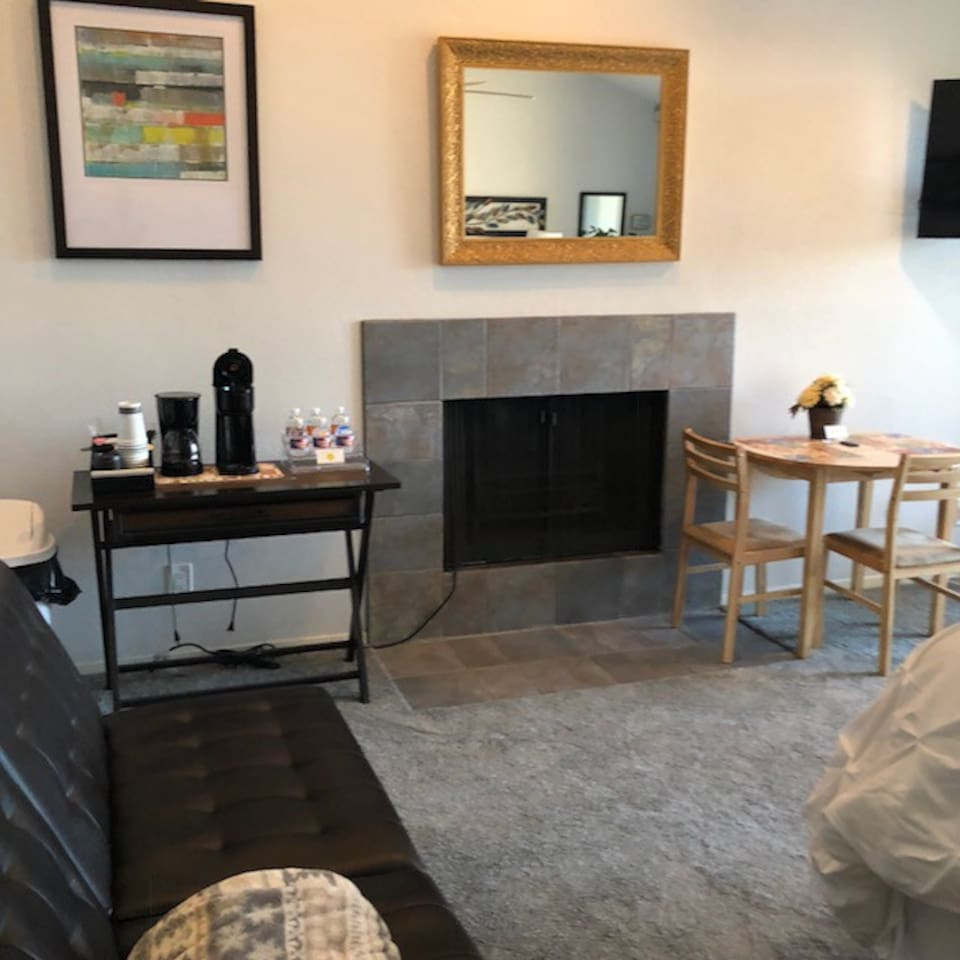 Table by fireplace and coffee bar with coffeemaker and a variety of K-cups