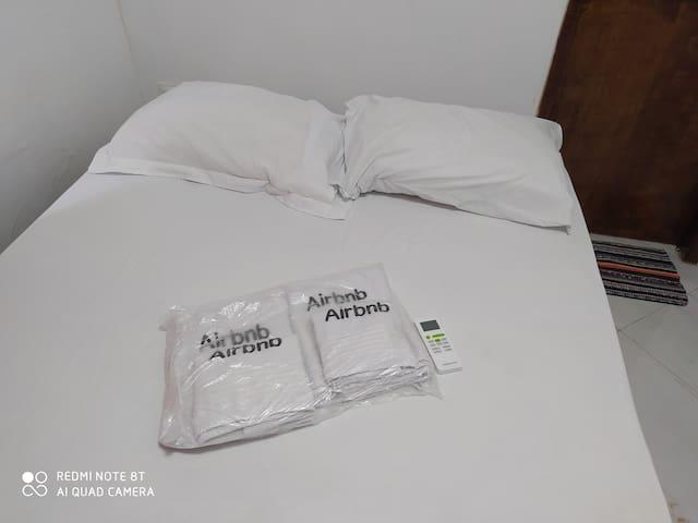 Mais foto do quarto casal suíte. Lençóis padronizado Airbnb controle ar-condicionado e ao lado banheiro banho quente e frio.
