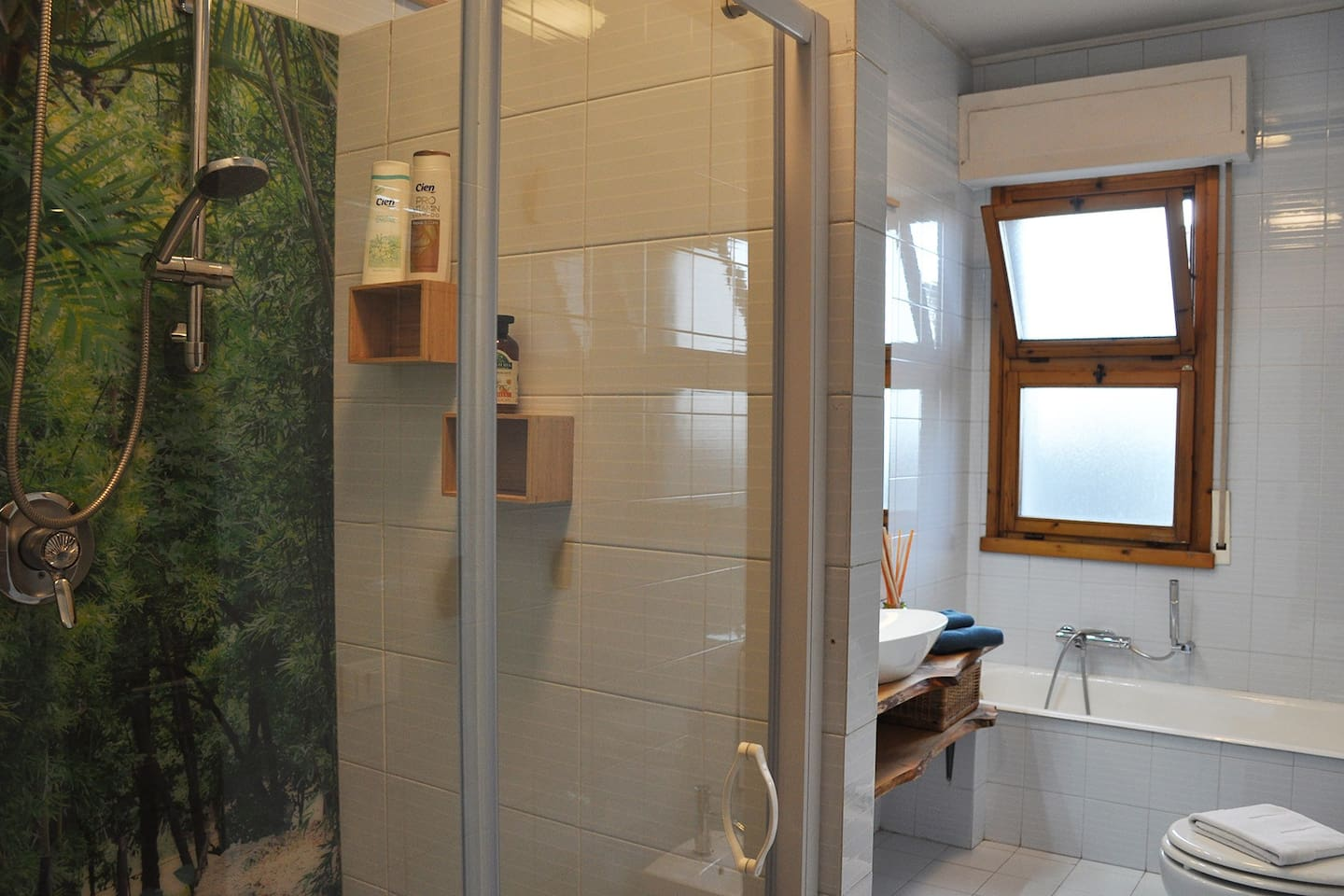 Shower with glass door and decorative wall.