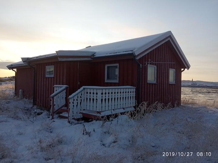 Rød hytte ved fjorden og Nesseby de Varanger