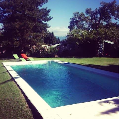 Villa piscine dans jardin arboré et verdoyant.