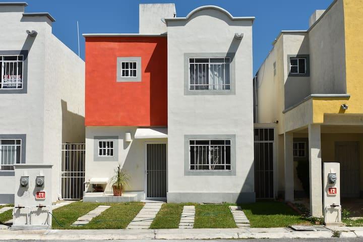 Casa K'iin Nah es una cómoda casa de dos niveles con dos lugares de estacionamiento. En la planta baja encontrarás la sala, comedor, cocina, medio baño y una amplia terraza con palmeras.  En la planta alta están las 3 recámaras y un baño completo.