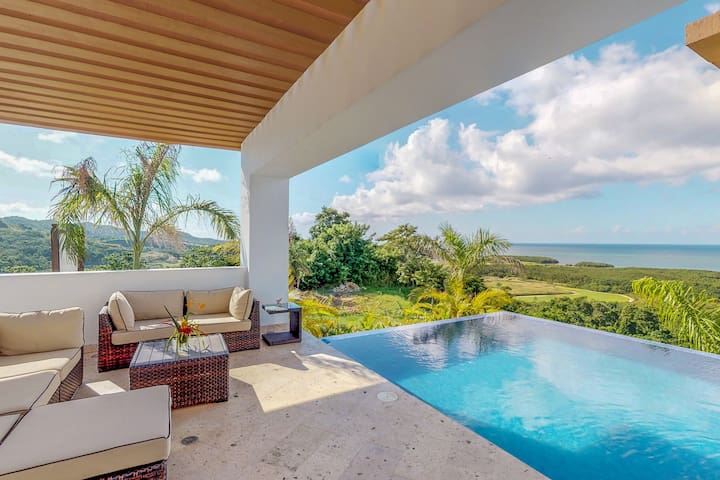 Gorgeous home w/ a large living area, outdoor infinity pool, & views of the sea
