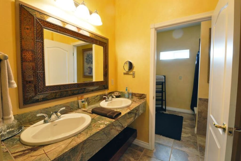 The en-suite bathroom includes his and her sinks and a separate tile shower.  A hairdryer and magnifying mirror are also provided.