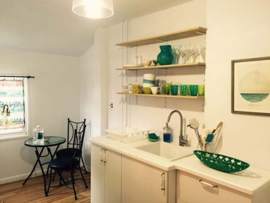 The kitchen contains a fridge, stove, toaster, plates, silverware and pots. a corner nook has a bistro table and 2 chairs , perfect for morning coffee.
