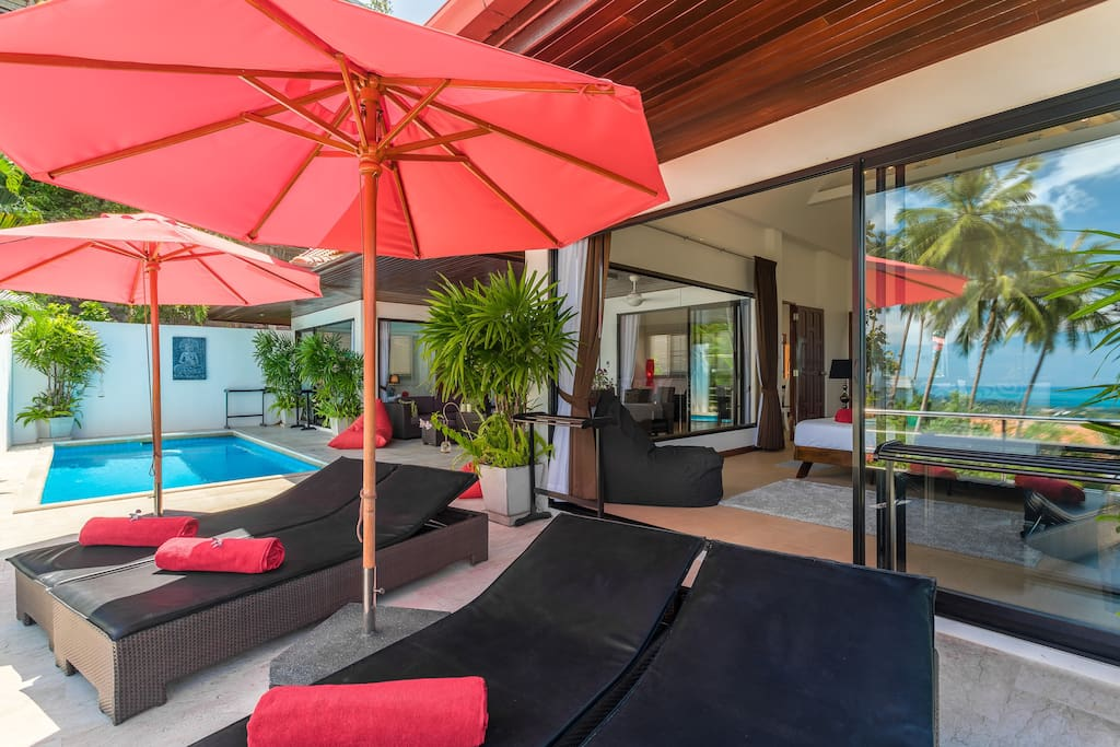 View of your villa with the reflection of the palm trees and the ocean in the large patio windows