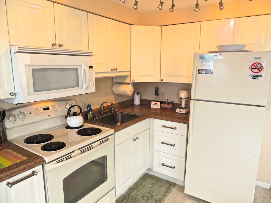 The kitchen in Apartment B has large appliances, with K-cup Cruisinart coffee maker, turn table microwave, toaster, blender, stainless steel sink with disposal, LED lights, full size GE 4 burner oven, dishes, utensils, ice maker, first day starter coffee & dish soap are provided.