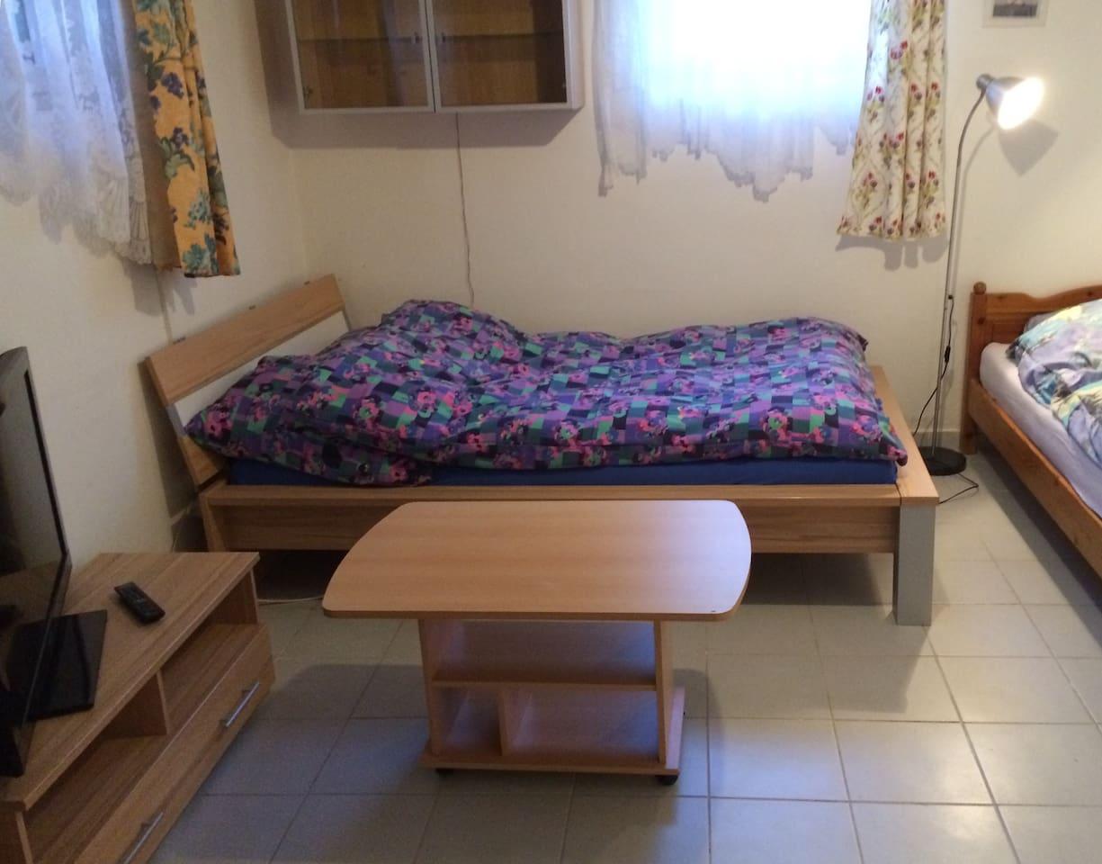 Schlafzimmer mit einem Doppelbett, einem Einzelbett und TV.
