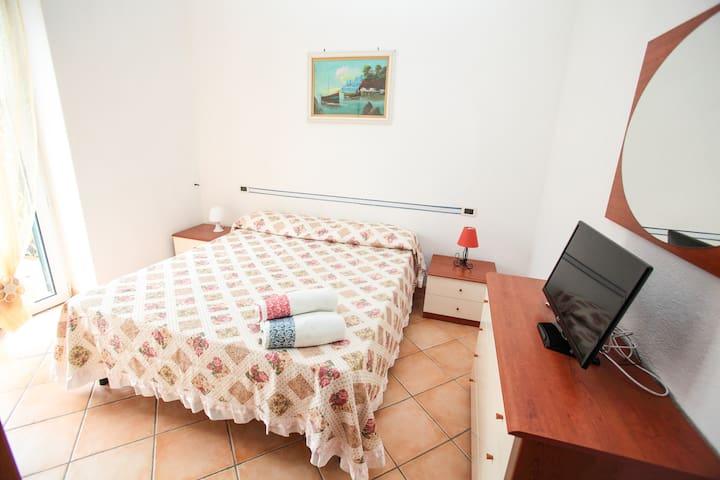 Camera da letto con armadio, cassettiera, tv LED, balcone su giardino