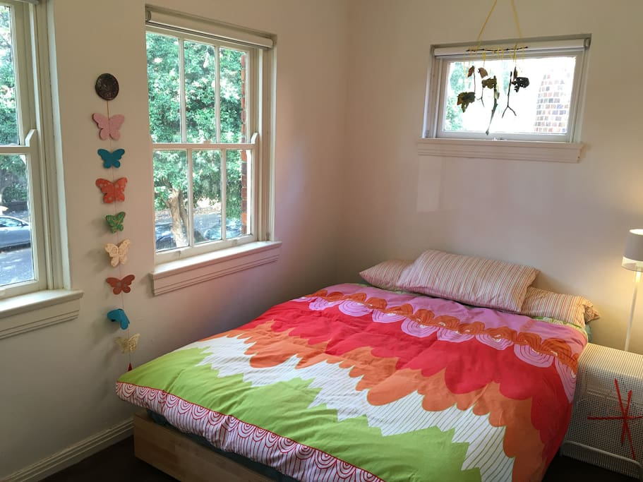 Bright room with a queen size bed and access to a small wardrobe.
