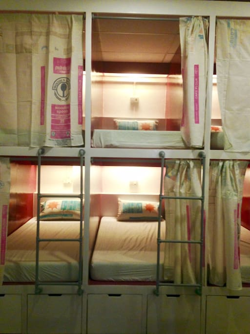 Pod-style or capsule type beds each with reading light, outlet,and recycled privacy curtain made from   flour sacks. Go green! =)