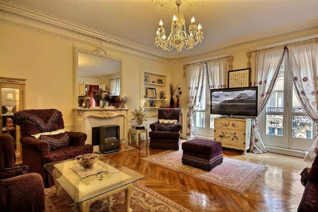 Living   The 30 square meters living room has 2 double glazed windows facing street and leading to the balcony . It is equipped with : 2 sofas, coffee table, cable, TV, DVD, 2 armchairs, built-in shelves, decorative fireplace, hard wood floor.