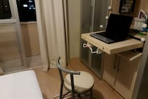 O quarto também dispõe de espaço para uso de notebook, com tomada ao alcance.