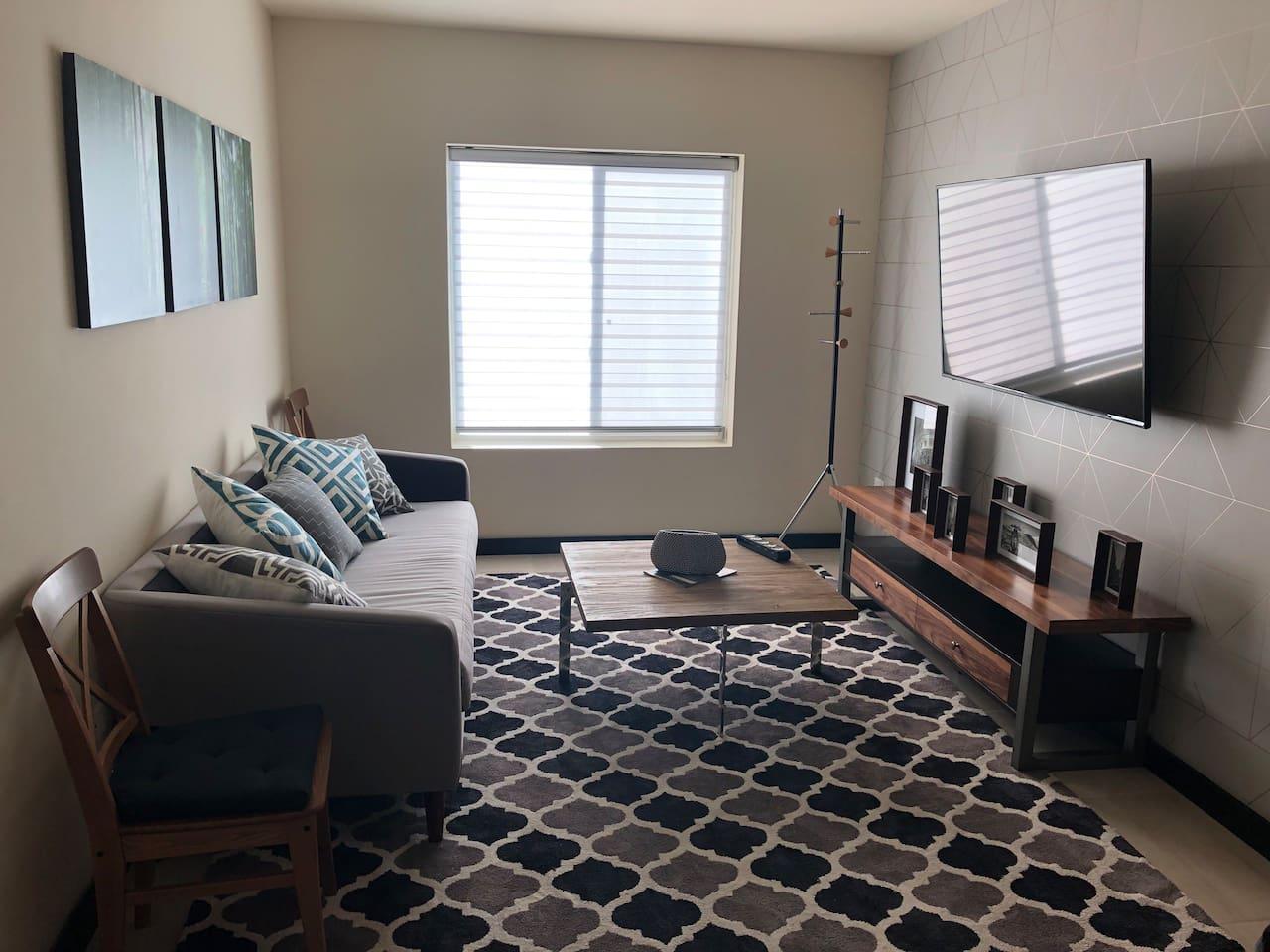 Large living room with television / Amplia sala de estar con televisión
