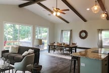 Open layout kitchen, dining room and living room with custom oversized sliding doors leading to the deck on two sides