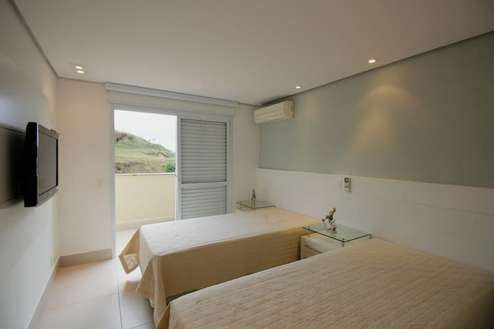 Suíte com duas camas de solteiro e ar condicionado  com vista para a Mata Atlântica.