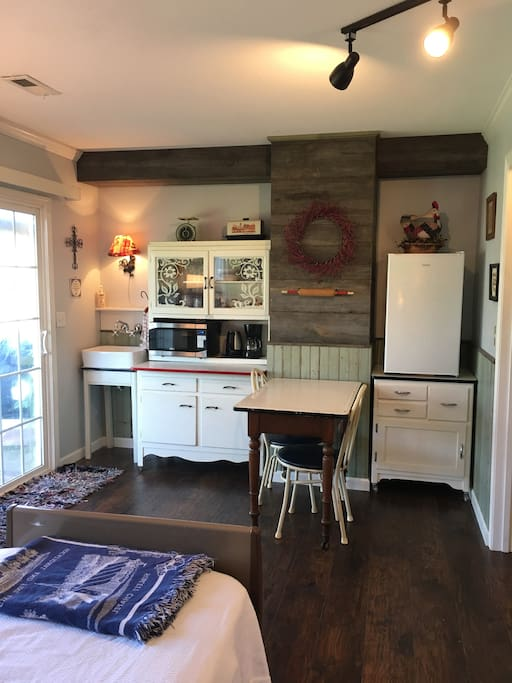 This cute old-timey kitchen has all the modern conveniences:  fridge, microwave, coffee and tea pots and running water.