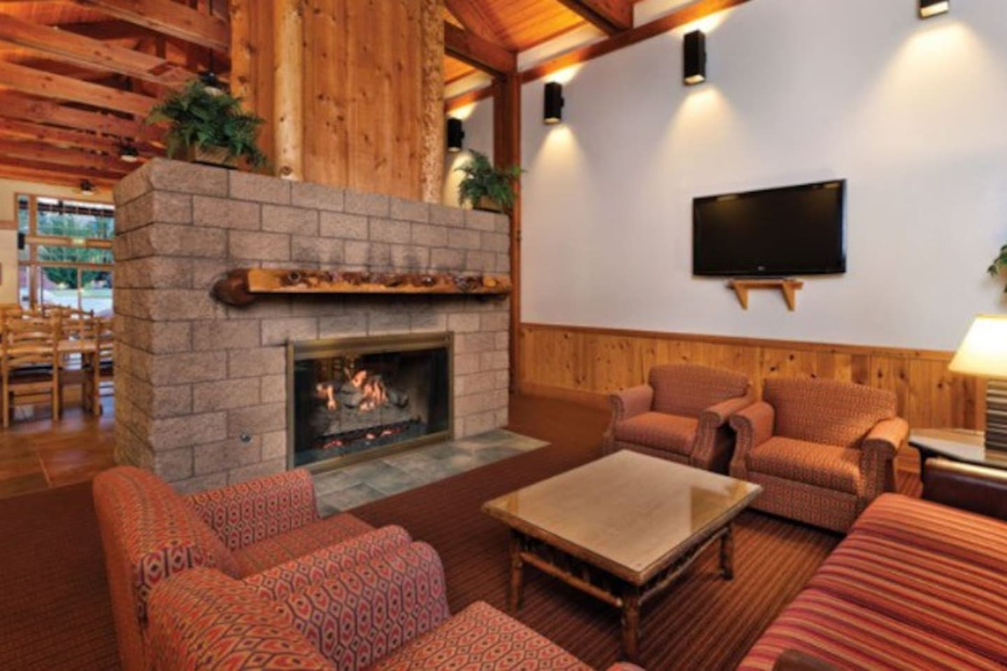 Huge Fireplace With Large Seating Area & Movies Playing On TV In Recreation Lodge