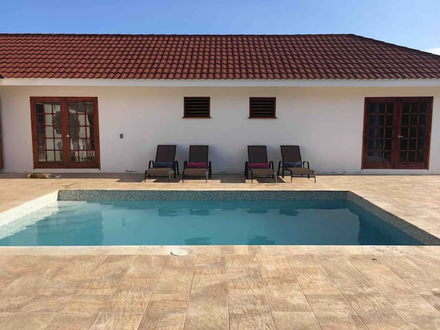 Sun drenched pool deck, directly accessible from the bedrooms and living room. Relax on a sun lounger or take a dip in the pool.
