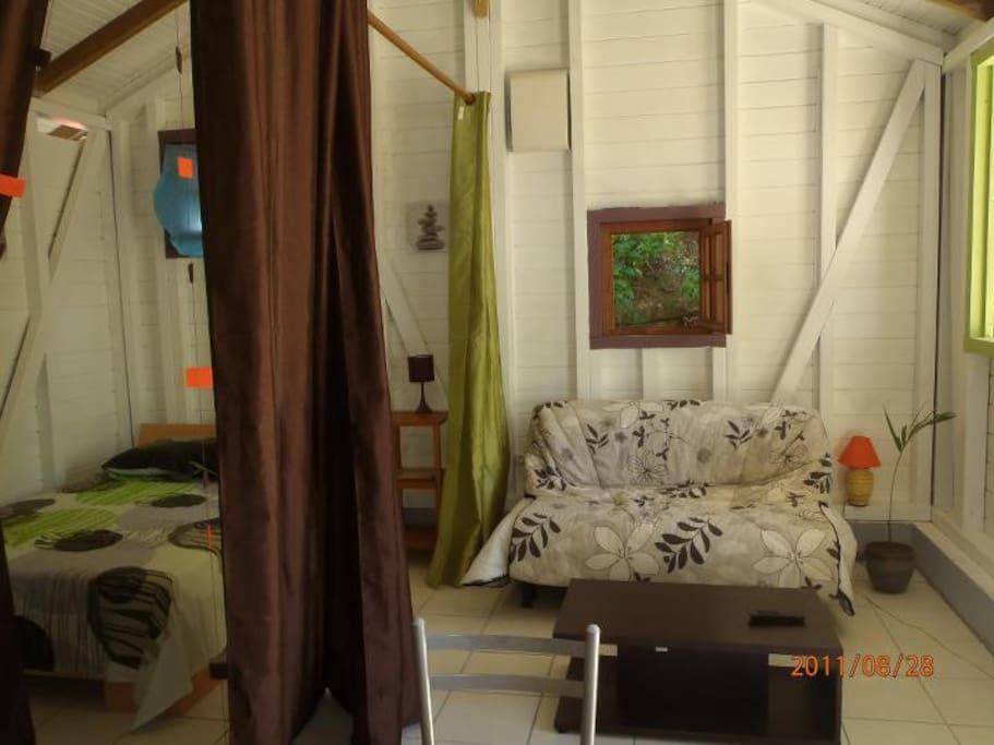 Un grand lit 2 places, et un canapé-lit 2 places, séparés par des rideaux
