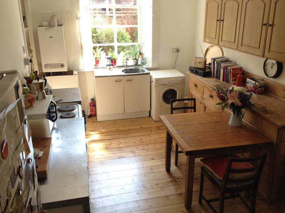 Bright, sunny kitchen with wooden floors and view of our shared garden