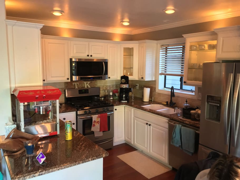 Kitchen with gas range, oven, microwave, coffee maker, toaster, and waffle maker