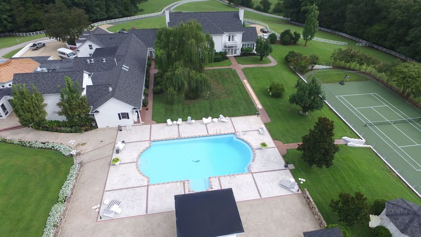 Aerial photo of the grounds from the rear of the property showcasing the resort 60 by 30 size private pool, private tennis court, with volleyball court and farm, etc just out of view.