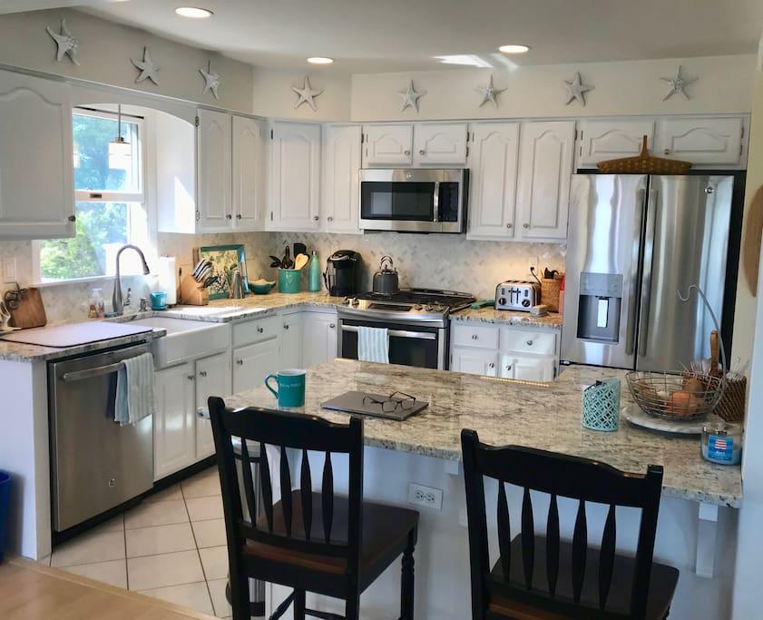 Kitchen w/granite counters, stainless appliances & farm sink.