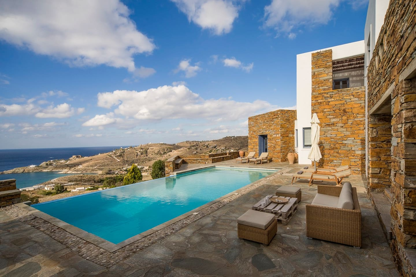 The outdoor spaces feature the classic elements of Cycladic design -think whitewashed walls and local stone