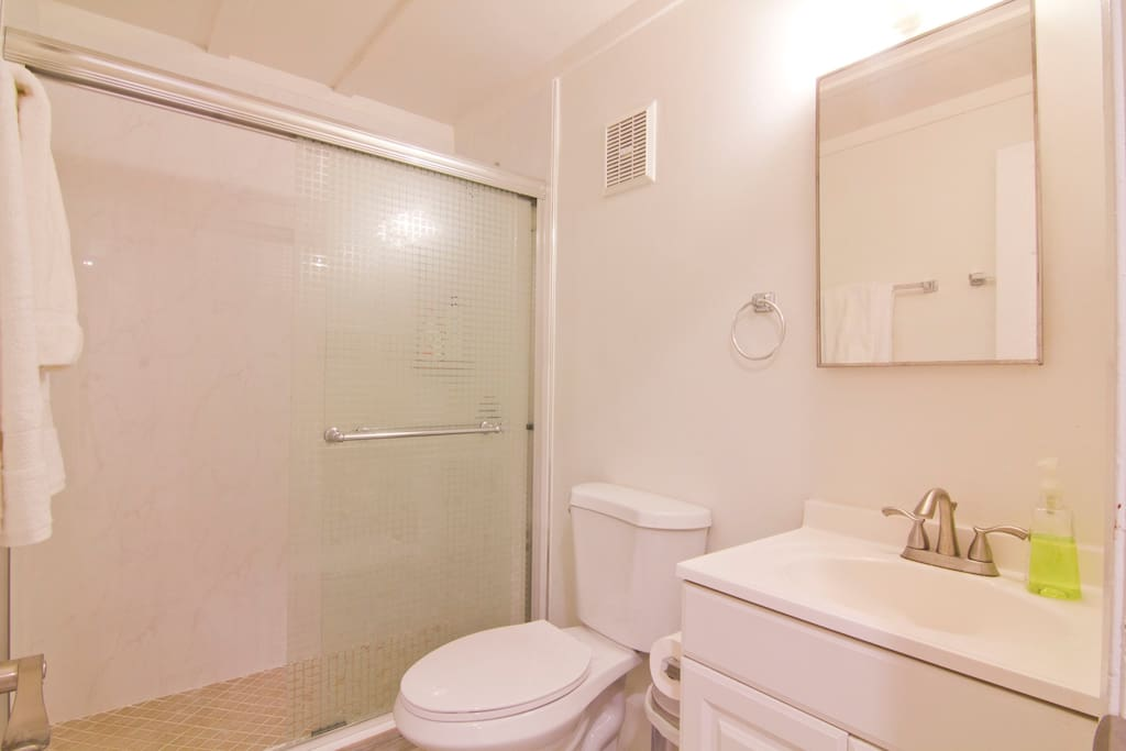 Brand new bathroom with walk in shower, tile flooring and modern design