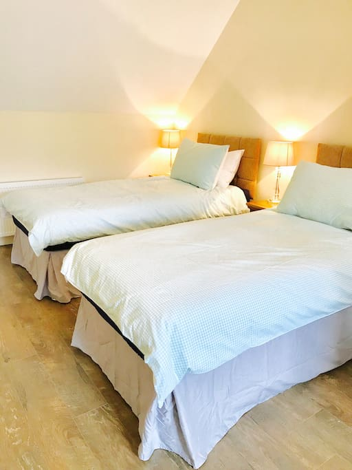 One half of large bedroom with two single beds. Each bed has its own bedside table. Lots of surface space and seating out of view.