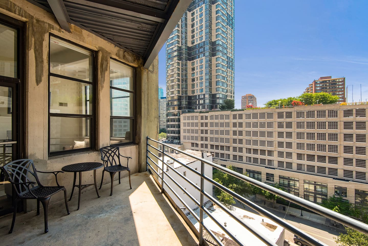 Private balcony with outdoor seating and table, with stunning city views