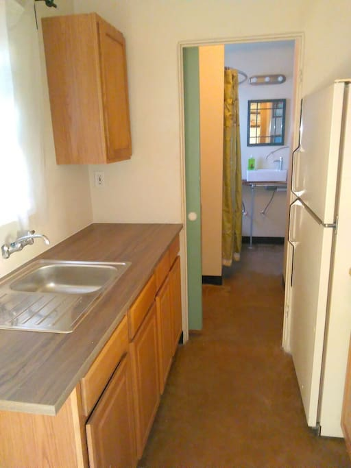 Open layout kitchen. Grey water from kitchen sink close to plants outside. Hallway leads to bathroom.