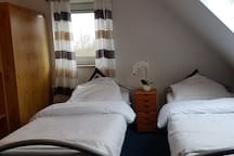 Bed room number 3 with 2 single beds, a wardrobe and desk