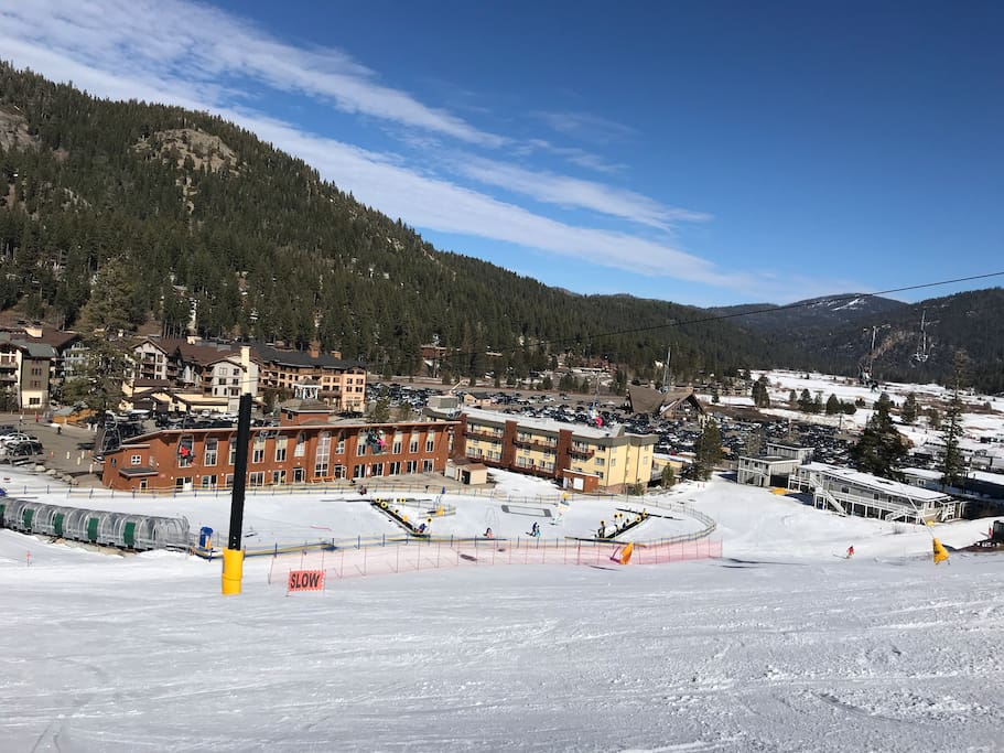 View of the Squaw Kids ski school Red Wolf Lodge next to it, and Squaw village in the background