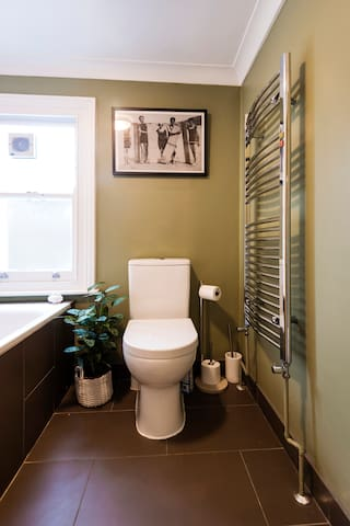 Family bathroom with bath and shower, heated towel rail, toilet, sink and additional storage.