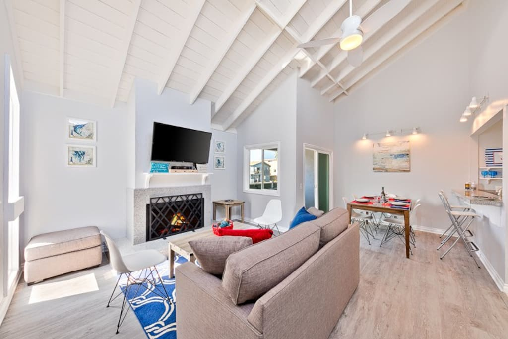 Clean, beach chic great room with a large flat screen TV, a fireplace, comfortable seating, and ceiling fan.