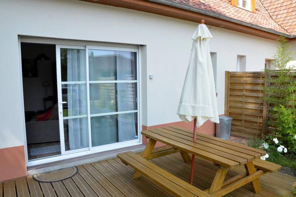Une grande terrasse avec des transats et un barbecue