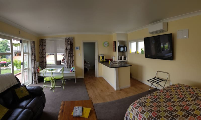 showing dining area, entrance to bathroom, kitchen and 60 inch TV