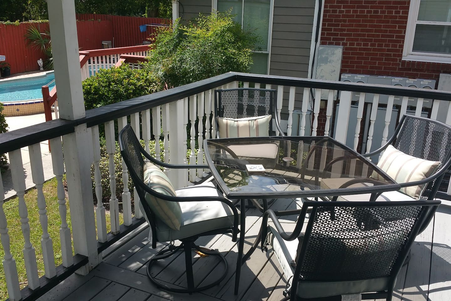 Private back deck with new glass top dining table and cushioned chairs.