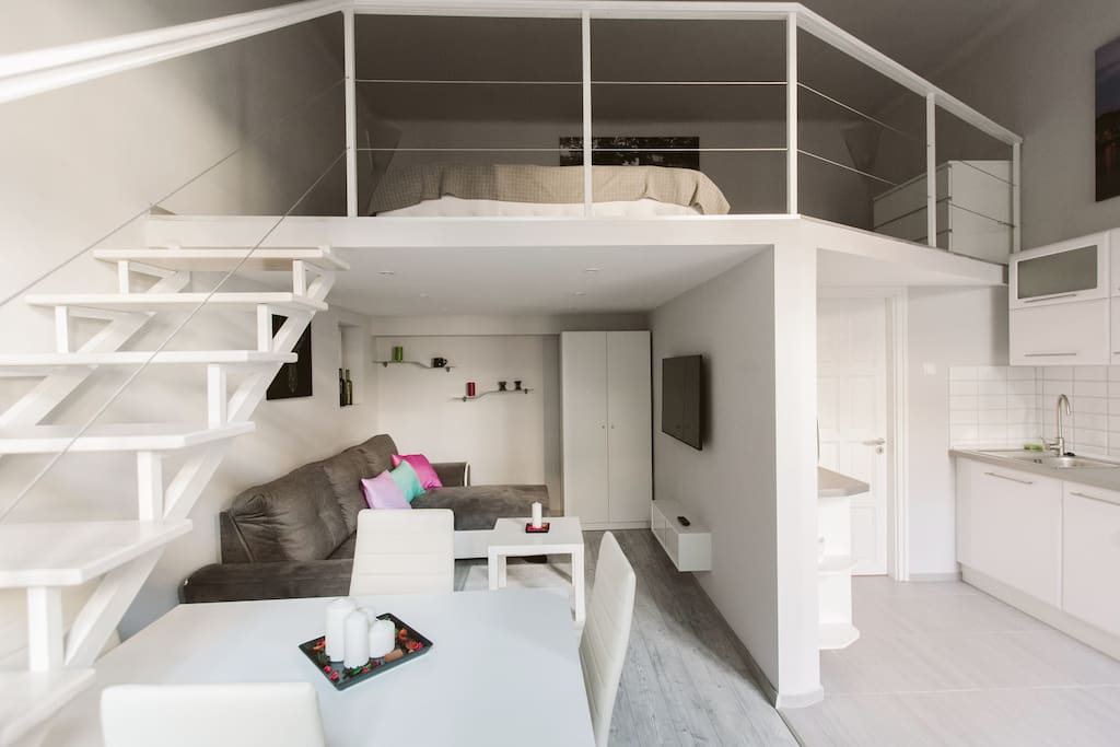 sleeping space on the mezzanine, living room and part of the kitchen with the entrance to the bathroom