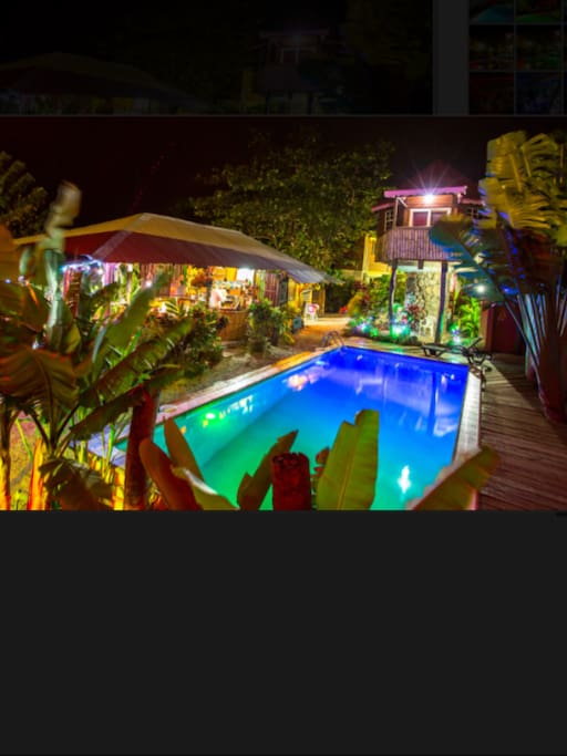 Nightime shot of the bar and swimming pool area at Calibishie Gardens