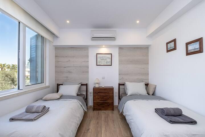 Спальня с двумя кроватями, рабочим столом, шкафом и видом на бассейн. Москитная сетка и закрывающиеся жалюзи.