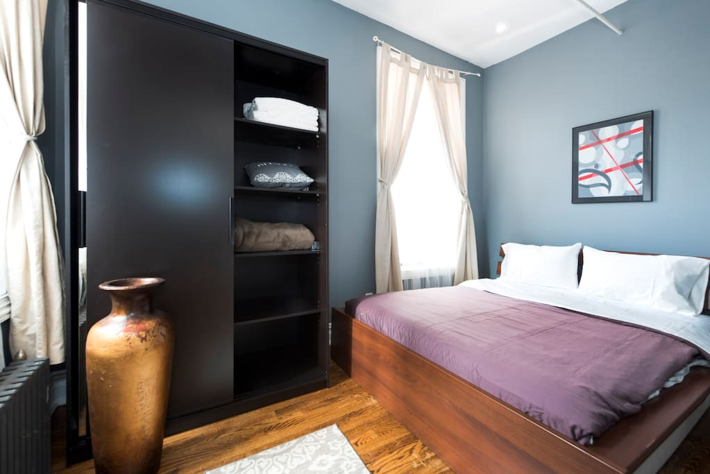 On the other hand, this sophisticated and chic-looking second bedroom offers an array of colors pleasing to the eye. The bed features a wooden finish -- a common theme running through the penthouse -- and is complimented by the sunlight thanks to a beautiful nearby window.