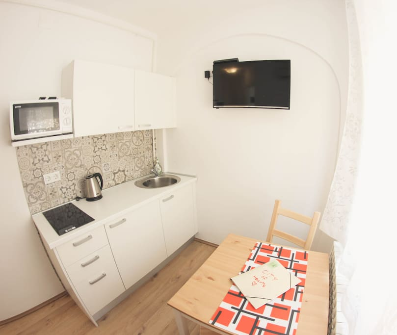 Main dining room with small kitchen and flat cable TV, aircondition, fridge, microwave oven, kettle and electric stove.