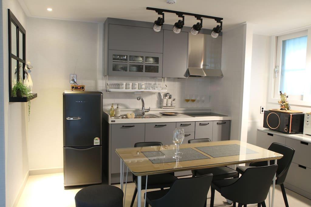 6인이 사용하실수있는 식탁, 냉장고, 정수기, 전자렌지, 전기렌지, 전기포트가 있는 주방입니다.