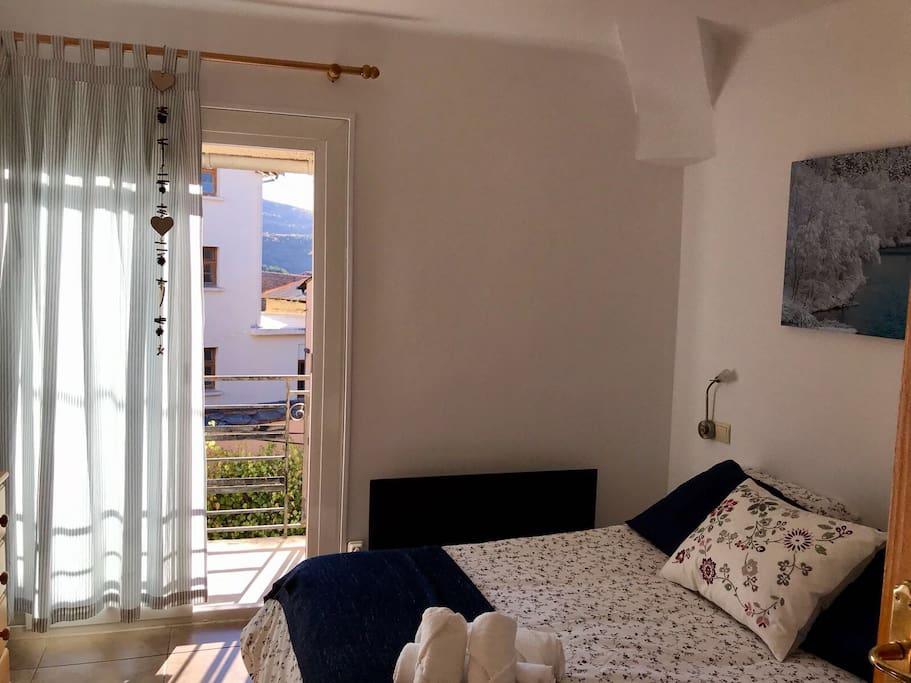 Habitación de matrimonio donde entra mucha luz por la ventana exterior donde hay un balcón.